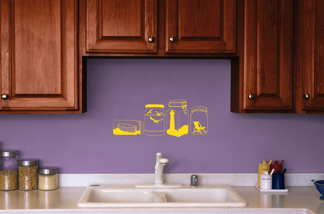 Yellow sea themed vinyl sticker on a purple wall in a kitchen just above a sink. Sea themed it shows four jars each containing a different element, a boat in the sea, three seagulls flying, a lighthouse surrounded by rocks and a deck chair.