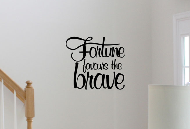 Fortune favours the brave, black vinyl wall art text in a hand written style designed to fit in a square. On a white wall in a living room.