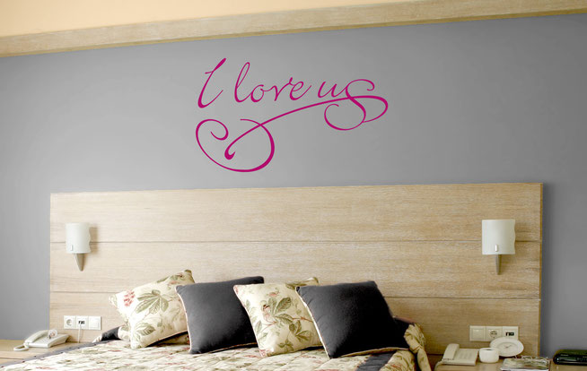 I love us swirly joined up handwriting quote in a pink vinyl on a grey wall in a bedroom.