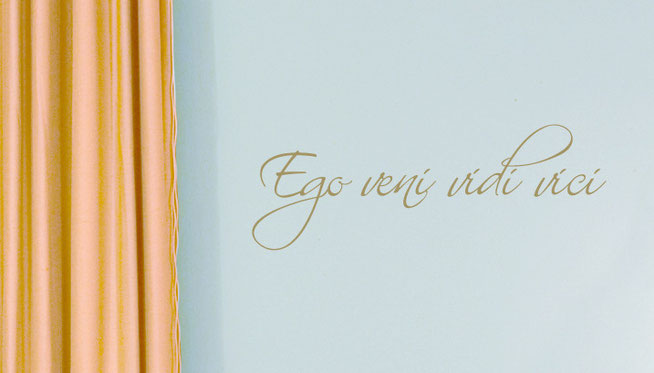 Ego Veni Vidi Vici - I came, I saw, I conquered, metallic gold wall art sticker in an elegant handwriting font, on a light blue wall near gold curtains in a living room.