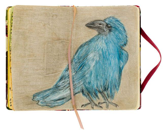 Auf einer Skizzenbuch Seite eine blaue Krähe gemalt mit einer goldigen Hintergrundfarbe.