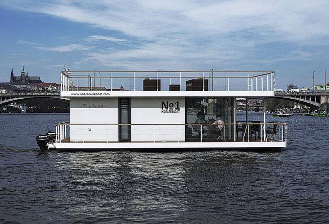 Vue de face extérieure n°4 du bateau où sont installés les interrupteurs d' Ecoome. Vue de face ou l'on voit les personnes dînant à l'intérieur et le bateau naviguant sur la rivière avec une ville en arrière plan.