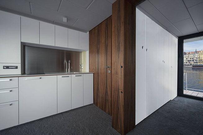 Cette image monte la cuisine et ses éléments laqué blanc avec plan de travail et son évier ainsi que une double prise de courant verticale se trouvant à droite de l'évier inox. La cuisine est ouverte sur le salon.
