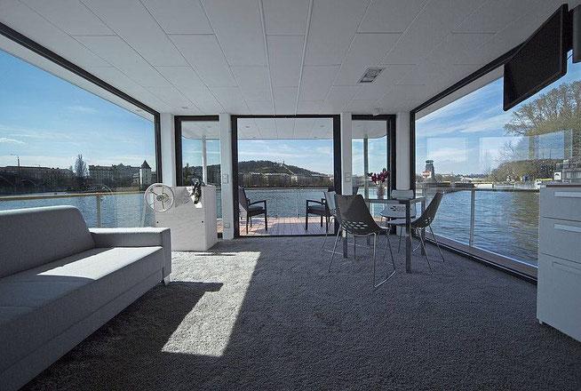 Cette photographie permet de voir le salon salle à manger au design épuré du bateau Houseboat n°1. On peut voir l'accessibilité des interrupteurs et des prises de courant à côté du poste de pilotage mais également à proximité de la terrasse extérieure.