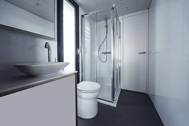 Ici, nous voyons le salle d'eau se situant sur le bateau comportant une douche vitrée, un vasque au design étroit posé sur un meuble vasque et entre ces deux éléments le toilette.