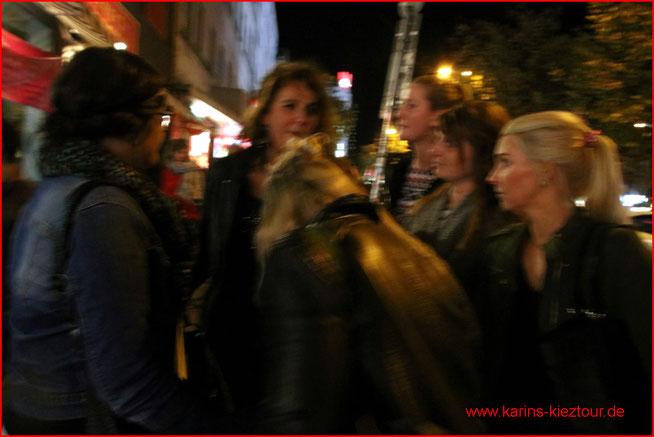 Karin steht inmitten einer Gruppe von jungen weiblichen Gästen auf ihrer Kieztour.
