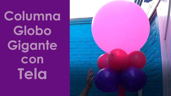 columna de globos con globo gigante y tela de colores
