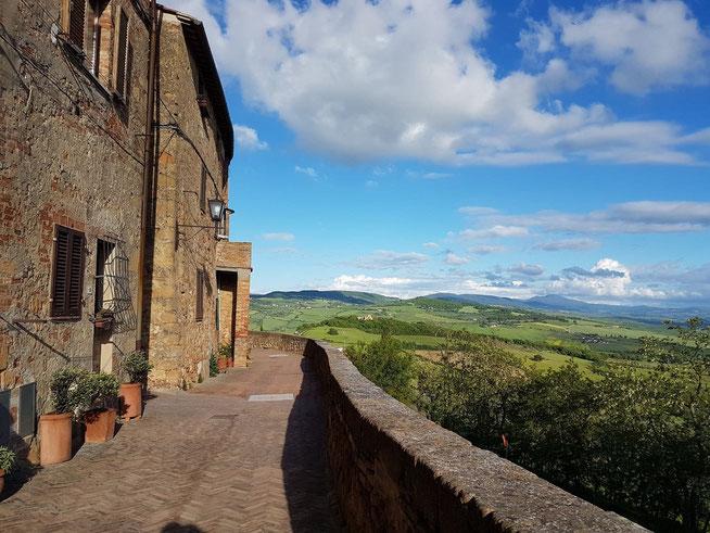 Ruelle de Pienza avec ses maisons de pierre et magnifique vue sur les collines du Val d'Orcia
