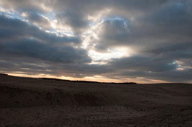 De foto is genomen op oudjaarsdag 2014 in de duinen achter de Haagse wijk Duindorp, waar de wind door de wolken door de duinen joeg. En dit prachtige plaatje tot stand bracht.