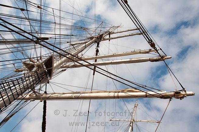 Dat een mast niet zomaar een houtenpaal met daaraan een zeil is, is te zien op deze foto. Allerlei verbinden zorgen ervoor dat de kracht die de wind erop uitoefent ervoor zorgt dat de boot vooruit gaat en de boel niet breekt.