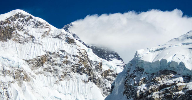 Wolkenverhangen, ragt der Mount Everest in der Bildmitte empor