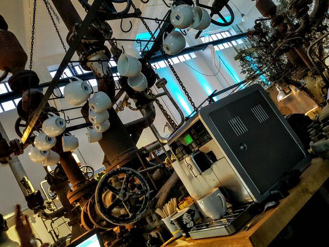 Kaffee Maschine vor industrieller Inneneinrichtung