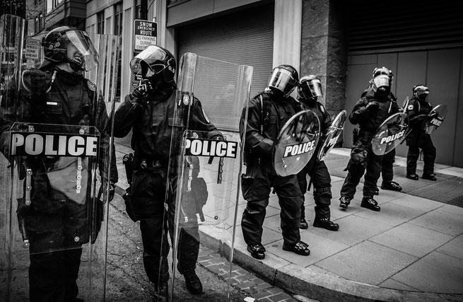 Polizeibeamte bei Protesten in schwarz-weiß