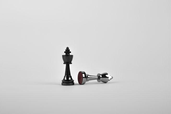 Zwei Schachfiguren - eine liegt
