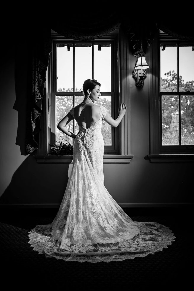 Black and white photo of a bride in front a window. Bride is shown from behind with face to the side. Dress is fanned on floor.