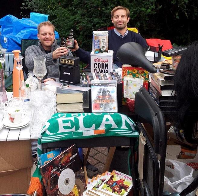 freaky routine, Flohmarkt, Flohmarkt-Stand, Trödel, 2 Männer stoßen mit Flaschenbier an