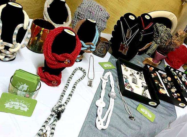 Tisch mit verschiedenen Produkten von Sabine Fölserl bei einer Ausstellung.