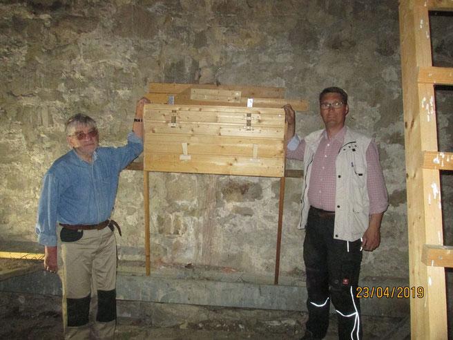 Zwei Männer in Arbeitskleidung stehen an einem großen Holzkasten an der Mauer