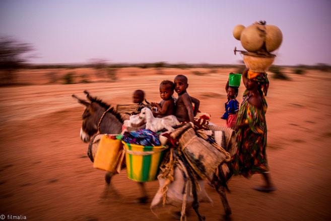 Familia de la tribu Peul con los enseres diarios desplazandose hacia otra zona