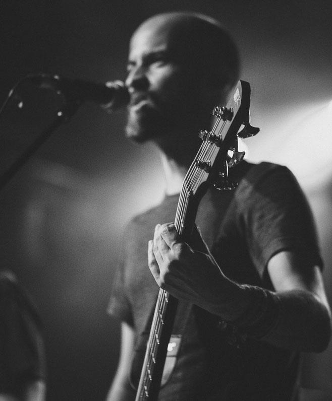 Musiker mit E-Bass der in ein Mikrofon singt