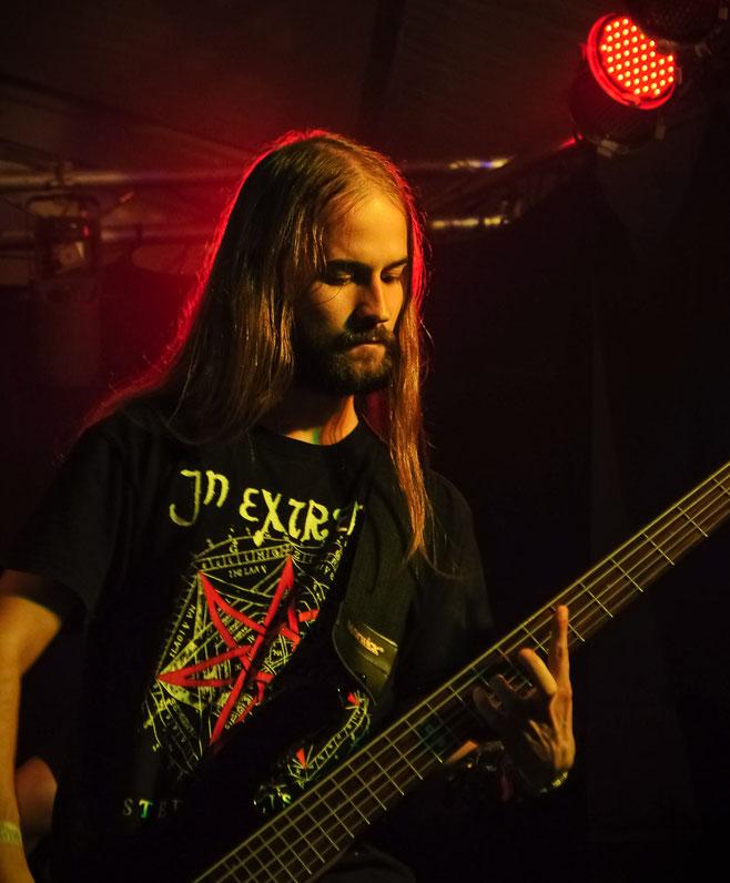 Musiker mit langen Haaren auf einer Bühne mit rotem Licht