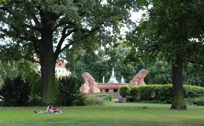 Menschen liegen auf der Wiese unter alten Bäumen. Arnswalder Platz in Berlin mit Stierbrunnen. Foto: Helga Karl