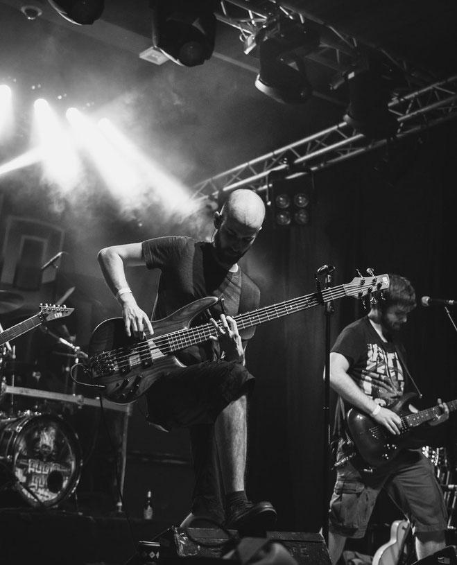 Bassist einer Metalband auf einer Konzertbühne mit Gegenlicht