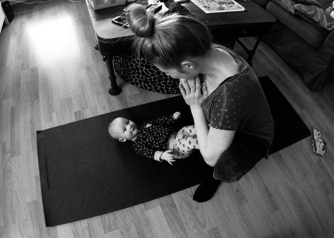 Yogamami mit Yogababy beim Yoga. Der Beckenboden gehört auch mit dazu