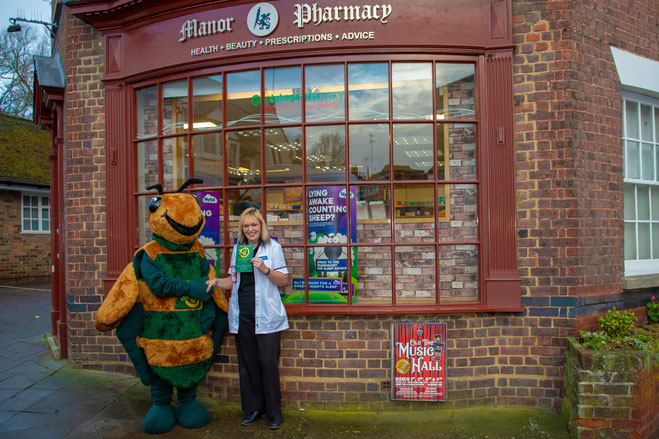 Manor Pharmacy staff member holding up a BILLY the Bee leaflet shaking hands with BILLY the Bee (Ben in the Billy the Bee costume)