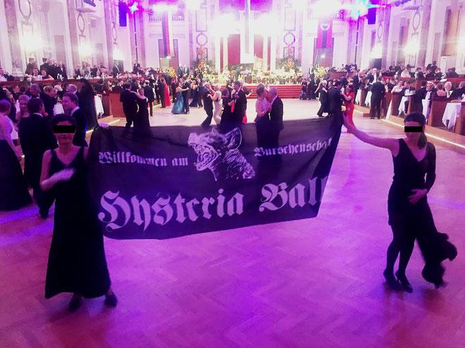 """Nogle aktivister kunne udklædt i elegante aftenkjoler smugle sig ind til festen og udrulle et banner med teksten : """"Willkommen zum Burschenschaft – Hysteria Ball"""""""