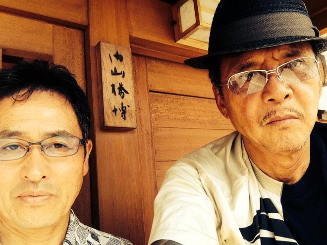 内山勝博宅玄関前にて、高塚久雄と竹垣悟の訪問記念ツーショット