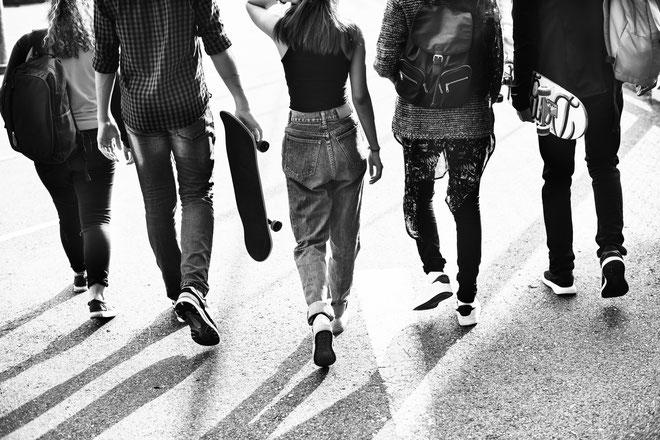 groupe-de-5-adolescents-qui-marchent-dans-la-rue-vue-de-dos