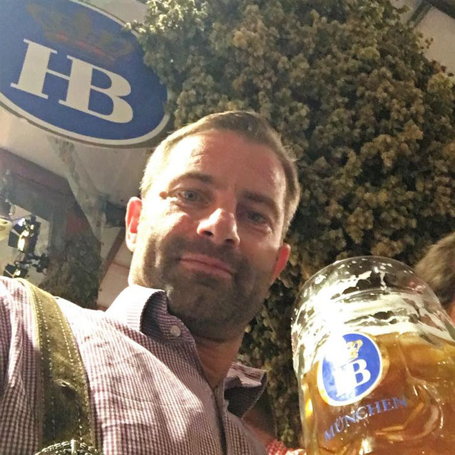 freaky finance, Oktoberfest, Wiesn, Hofbräuzelt, Mann mit Bierkrug, Hopfen im Hintergrund
