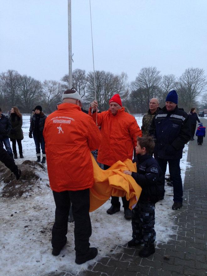 De voorzitter met zijn jongste kleinzoon Tijs, hijsen de nieuwe club vlag.  De vlag en oranje bestuurs jassen zijn geschonken door Jaap Kaan, Jan Kater, Kees van Bruggen, Jaap Oostindier en Klaas Hemke!