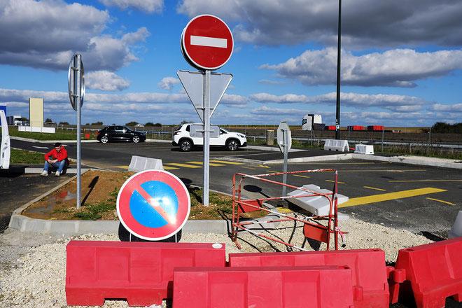 Mathieu Guillochon photographe, sur la route, autoroute, couleurs, station service, signalisation, panneaux, homme assis, ciel, nuages
