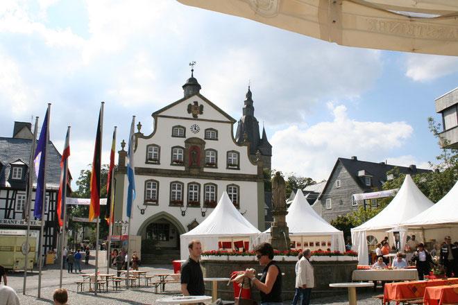 """Irgend einen Grund zum Feiern finden die Briloner immer: Marktplatz mit Petrusbrunnen, genannt """"Kump"""", Rathaus (und Propsteikirchturm im Hintergrund)"""