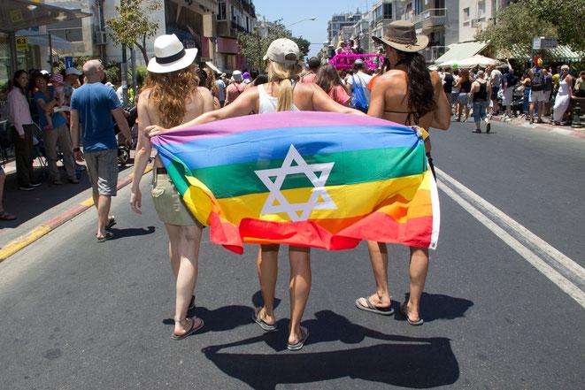 Chicas lesbianas o bisexuales hondeando la bandera LGBT durante Desfile de Orgullo Gay en Tel Aviv, Israel