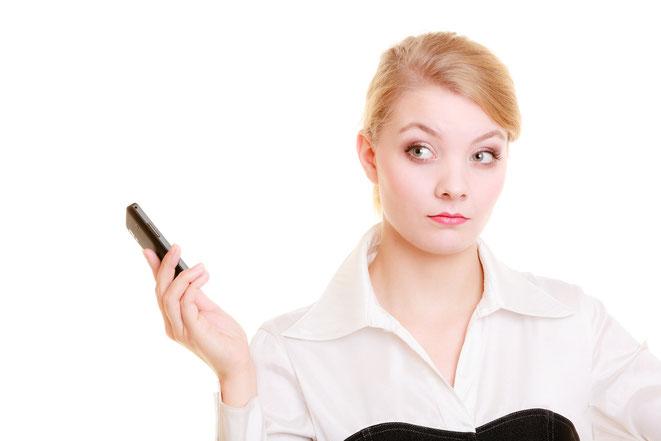 Frau hält Handy mit strengem Blick von sich weg. Aaden Detektei Leipzig, Detektiv Leipzig