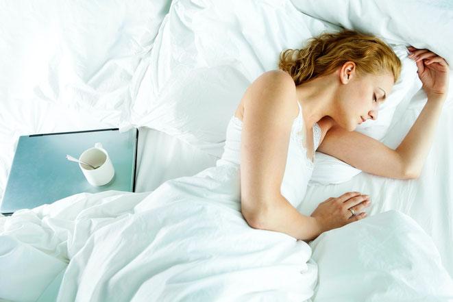 femme-qui-dort-sur-lit-blanc-avec-ordinateur-a-cote-d-elle-et-tasse-de-cafe-vide