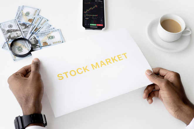 """freaky finance, Investitionsmöglichkeiten für Anfänger, Hände halten ein Blatt mit der Aufschrift """"Stock Market"""", Geld und Lupe, Kaffeetasse, Mobiltelefon"""