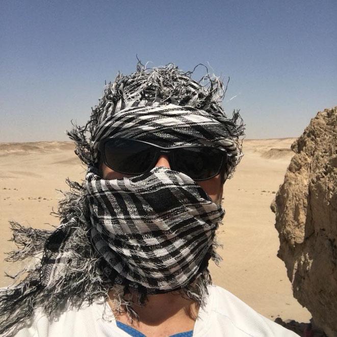 freaky finance, Ägypten, Wüste, Mann mit Tuch und Sonnenbrille im Gesicht steht in der Wüste