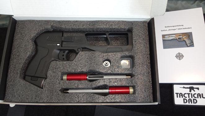 """Das hier ist der Lieferumfang den man für etwa 350 Euro bekommt, die Pfeilpistole, zwei komplette Patronen mit Pfeilen, ein Ladeadapter und jede Menge """"Berstscheiben""""."""