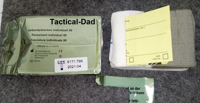 """Die schweizer Armee verwendet das """"Verbandpäckchen individuell 90"""". Ein stabil verpackter Militärverband mit großer Wundauflage, Verwundetenzettel und zusätzlicher Binde."""