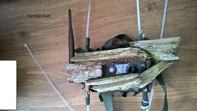 Die Tarnblende für die Wildkamera haben wir aus trockenen Holzteilen zusammengesetzt mit einem Tacker, Messer und Heißkleber. Die Kabelbinder waren zum Befestigen an der Wildkamera.