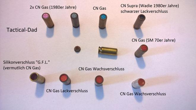 Diverse CN Gas Patronen. Die links unten mit rotem Silikonverschluss und die rechts oben mit schwarzem Lackverschluss sind extrem selten.