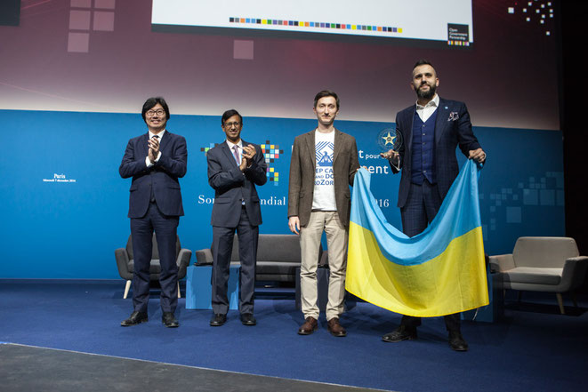 Yuriy Bugay is on stage with Max Nefyodov, first deputy minister at Ministry of Economic Development and Trade of Ukraine, holding a Ukrainian flag as they are about to receive the First prize at OG. Open Government Partnership/Photograph by Evan Abramson
