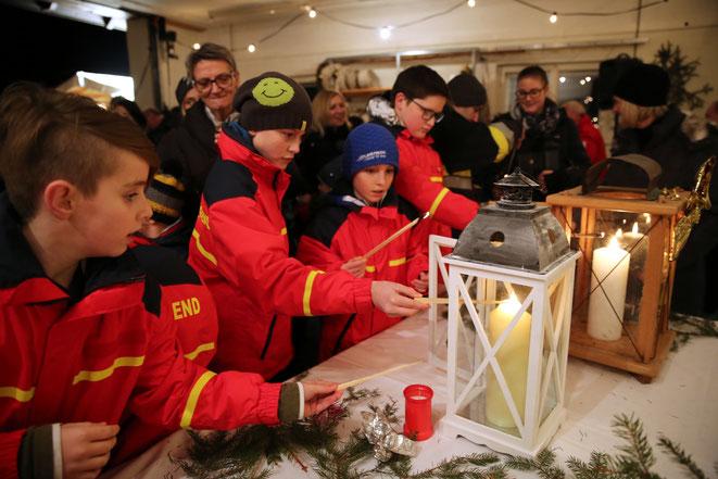 die Feuerwehrjugend Steinfeld übergibt das Friedenslicht der Bevölkerung
