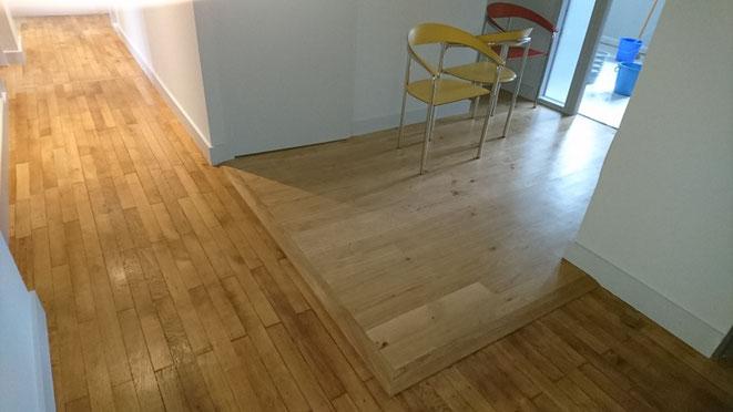 appartement transformé en bureau, nous avons posé un parquet chêne sur la partie en carrelage et placé 2 seuils suisse pour récupérer la différence de niveau