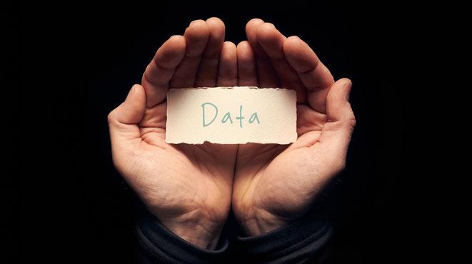 """Hände, die einen Zettel mit der Aufschrift """"Data"""" (Daten) halten; Aaden Detektei Berlin"""