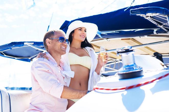 Mann mit Frau im Bikini und mit Champagner-Glas auf einer Yacht; Aaden Detektei Berlin